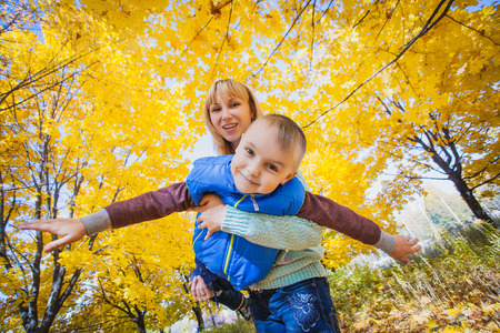 Young mother and her kid have fun in the autumn park photo