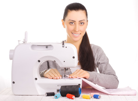 modiste: happy seamstress sewing. isolated on the white