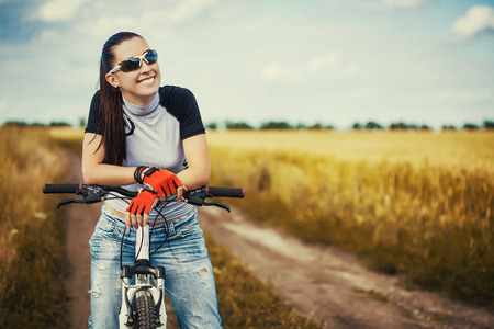 Woman is riding bicycle outside in the field photo