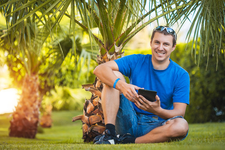palm garden: man with tablet in the palm garden