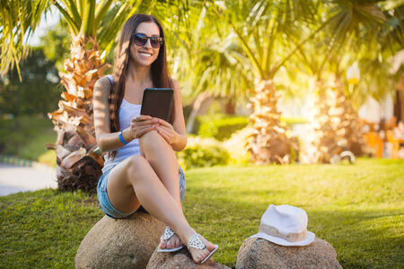 palm garden: girl with tablet in the palm garden
