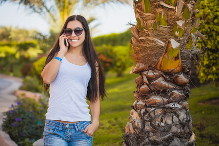 palm garden: girl is talking on the phone in the palm garden