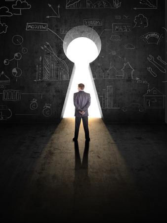 businessman against black wall with key hole photo