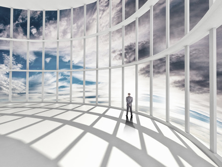 businessman standing in office and looking at sky in window photo