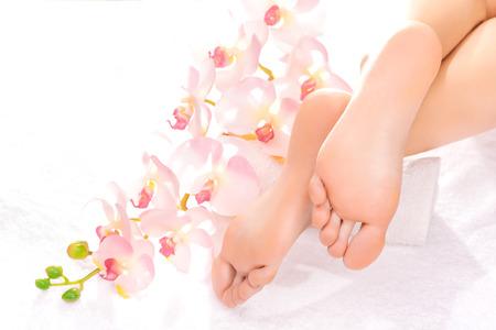 reflexologie plantaire: Massage des pieds dans le salon de spa avec orchidée Banque d'images