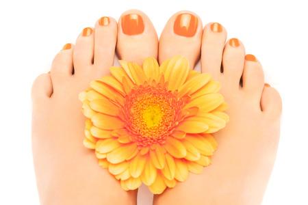 pedicura: hermosas uñas pintadas de color naranja con gerbera