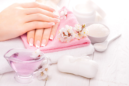 manicure salon: french manicure with essential oils, apricot flowers. spa Stock Photo