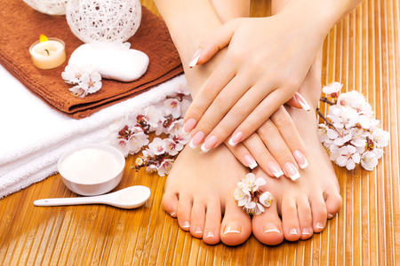 woman in bath: brown manicure and pedicure on the bamboo