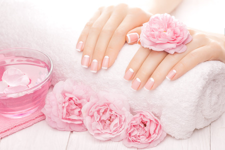 mujer con rosas: manicure francés con flores color de rosa. spa