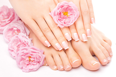 pink nail polish: pedicure and manicure with a pink rose flower Stock Photo