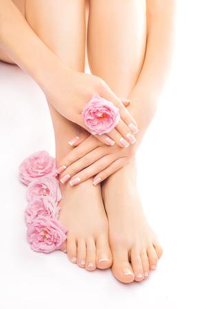 manos y pies: pedicura y manicura con una flor rosada se levantaron