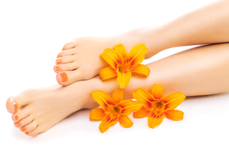 french pedicure with a orange lily flower isolated on the white Stock Photo
