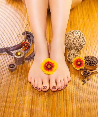 french pedicure: french pedicure with a orange flower on a bamboo background Stock Photo
