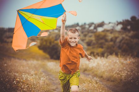 kite: Happy kid running across the field with kite flying over his head Stock Photo