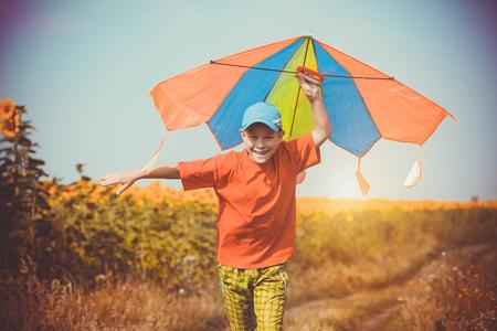 papalote: Niño feliz que se ejecuta a través del campo con la cometa volando sobre su cabeza