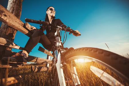lifestyle: Bonne jeune femme à cheval vélos à l'extérieur. Mode de vie sain.