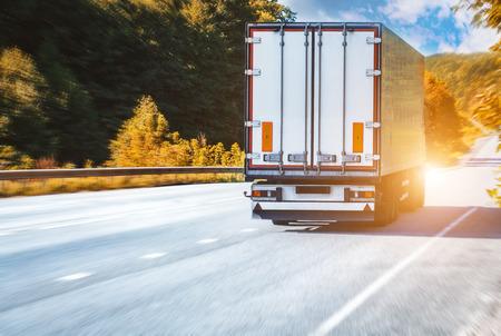 White truck on the asphalt rural road on the sunset