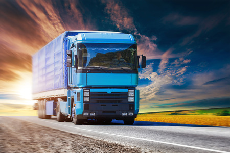 Blue truck is driving on the sunset highway Stock Photo