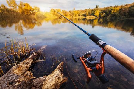 Canna da pesca vicino al bellissimo laghetto sul tramonto Archivio Fotografico - 47323399