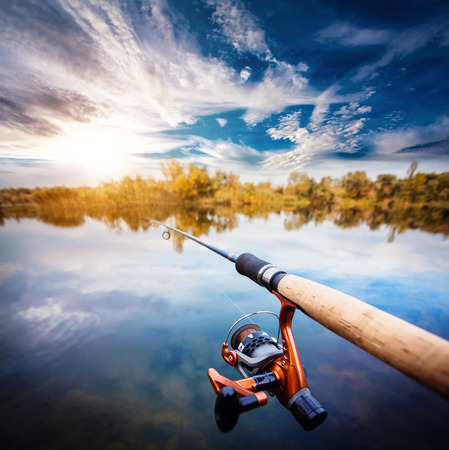 fishing pier: Fishing rod near beautiful pond with beautiful cloudly sky