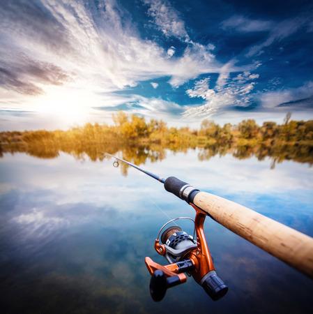 Fishing rod near beautiful pond with beautiful cloudly sky
