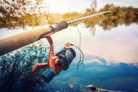 Fishing rod near beautiful pond in the morning