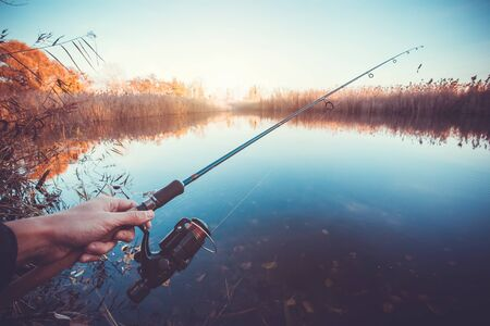 hand line fishing: hand with spinning and reel on the summer lake