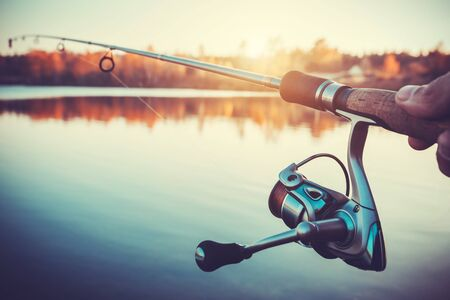 spinning reel: hand with spinning and reel on the summer lake