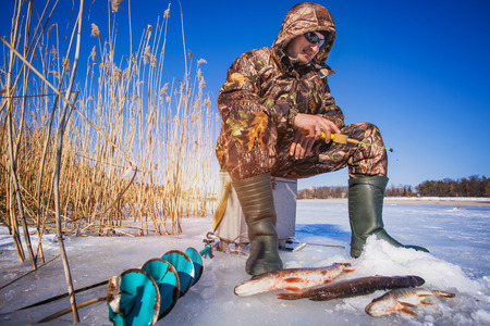 tip up: Happy ice fisherman holding a pike caught on a tip up Stock Photo