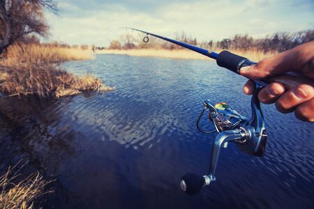 fishing reel: hand with spinning and reel on the summer lake