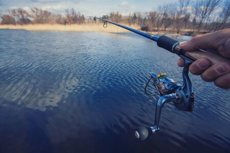 jigging: hand with spinning and reel on the summer lake