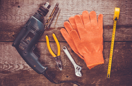 work gloves: Dirty set of hand tools on a wooden panel
