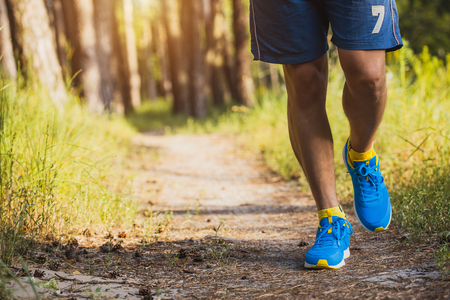 athlete running through the woods. Feet, bottom view