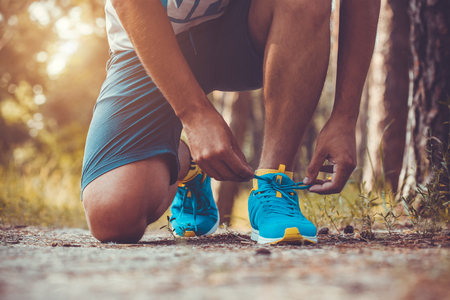 sport shoe: Runner tying shoelaces on sneakers. Morning jogging in the forest Stock Photo