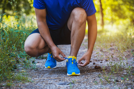 shoe string: Runner tying shoelaces on sneakers. Morning jogging in the forest Stock Photo
