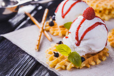 sweet and savoury: Vanilla Ice Cream with Mint and waffles. Homemade Organic product. On the black wooden table.