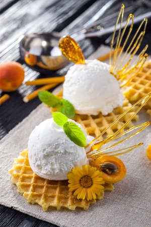 sweet and savoury: Ice Cream with apricot, Mint and waffles. Homemade Organic product. On the black wooden table.