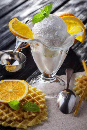 sweet and savoury: Ice Cream with orange, Mint and waffles. Homemade Organic product. On the white wooden table. Stock Photo