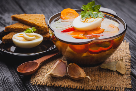 unprepared: Fresh vegetable soup in a pot on the black wooden background Stock Photo
