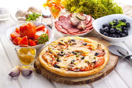 Delicious italian pizza and ingredients served on the white wooden table