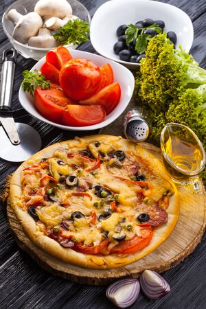 Delicious Homemade pizza and ingredients served on the black wooden table Stock Photo