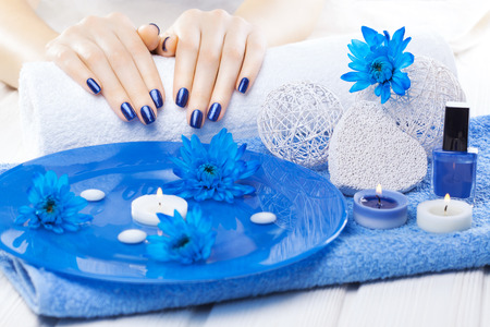 beautiful blue manicure with oil and candles, chrysanthemum and towel on the white wooden table. spa