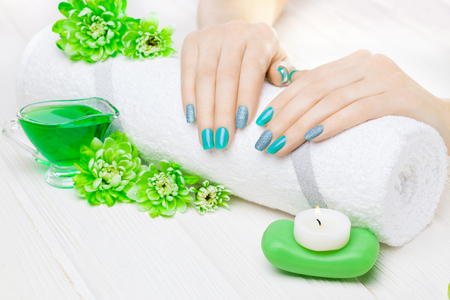 beautiful turquoisemanicure with oil and candles, chrysanthemum and towel on the white wooden table. spa