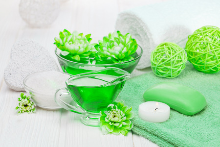 Spa still life of sea salt and essential oils and green chrysanthemum flowers Stock Photo