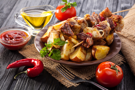 Meat skewer with herbs With onions, baked potatoes, tomatoes and greens on the black wooden table Stock Photo