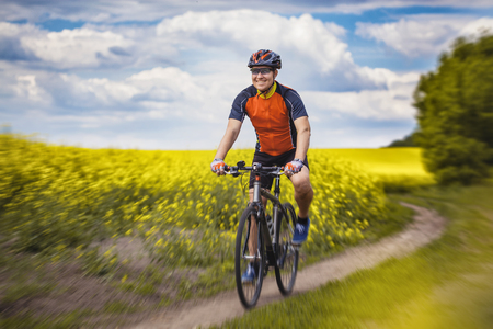 canola: A male cyclist is riding on a picturesque yellow rapeseed field. Sports, active recreation.