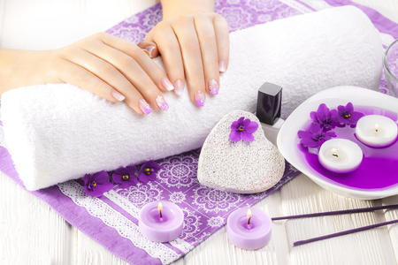 Luxury purple manicure with violet, candle and towel on the white wooden table. Women's hands