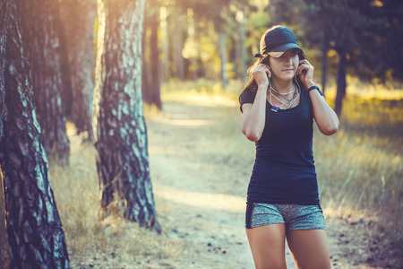 shoe strings: Beautiful athletic woman listening music on a run in the woods