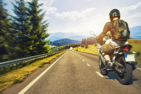 Motorcyclist rushes along the picturesque mountain highway