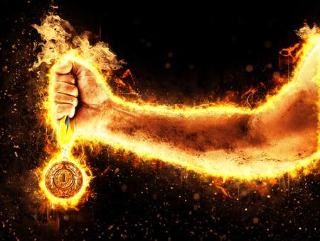 La main de Mans dans un feu tient la médaille d'or. Gagnant dans une compétition.